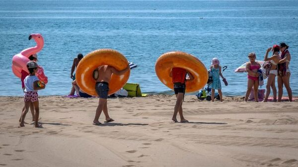 Children walk on the beach with rubber rings around their necks — and a pink flamingo — in Narbonne-Plage during a sunny day of summer on July 3, 2019.