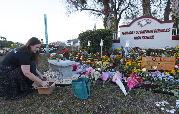 Suzanne Devine Clark, an art teacher at Deerfield Beach Elementary School, places painted stones at a memorial outside Marjory Stoneman Douglas High School during the one-year anniversary of the school shooting on Feb. 14, 2019, in Parkland, Fla. The state passed its red flag law in 2018 after the shootings at the high school.