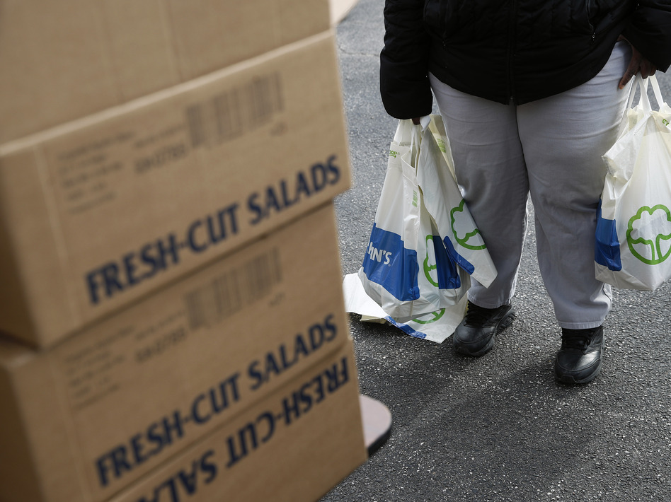 An FDA contract worker collects food and supplies from a food pantry in Baltimore. In the face of a Trump administration proposal that could cause 3 million people to lose federal food assistance, mayors from 70 cities are pushing back. (Patrick Semansky/AP)