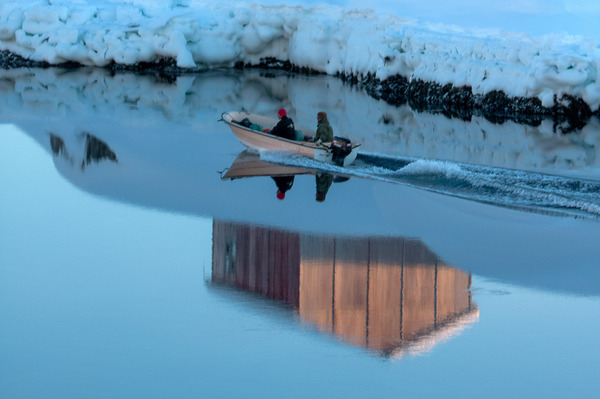Hunters head out to sea in a motorboat in Tiniteqilaaq, Greenland.