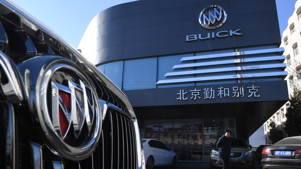 A woman stands outside a Buick showroom in Beijing on Dec. 15, 2016. China is imposing new tariffs on imported U.S. autos and auto parts.