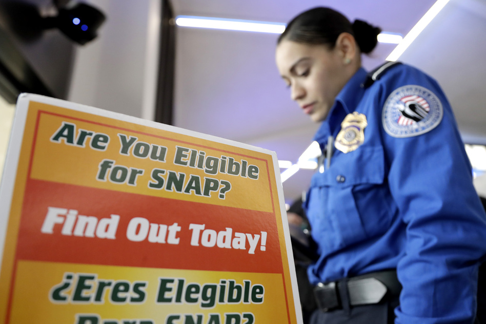 A Transportation Security Administration employee stands at a booth to learn about a food stamp program at a food drive at Newark Liberty International Airport, on Jan. 23, 2019, in Newark, N.J. A number of new rules and actions proposed by the Trump administration could affect poor or low-income people who use government safety net programs. (Julio Cortez/AP)