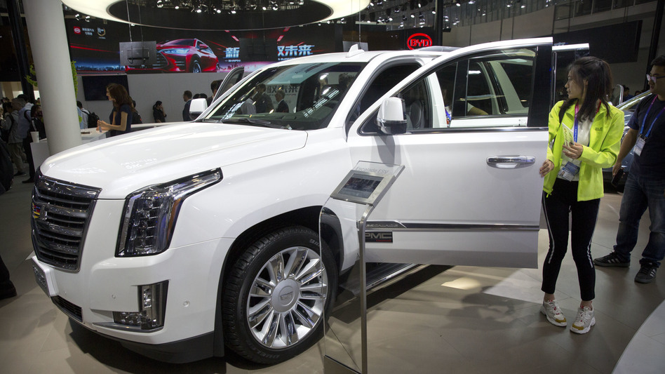 Visitors look at a Cadillac Escalade at the China Auto Show in Beijing in 2018. For General Motors, China is a bigger market than the United States. (Mark Schiefelbein/AP)