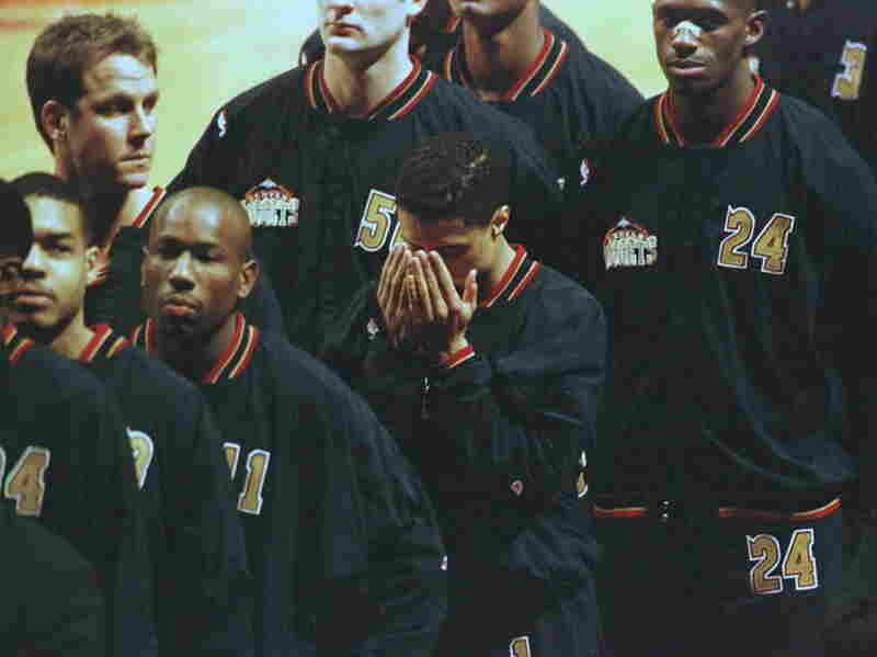 Denver Nuggets guard Mahmoud Abdul-Rauf bows his head in prayer during the singing of the national anthem before playing the Chicago Bulls on March 15, 1996. Abdul-Rauf was suspended for one game after refusing to stand for the national anthem, but reached a compromise with the NBA.