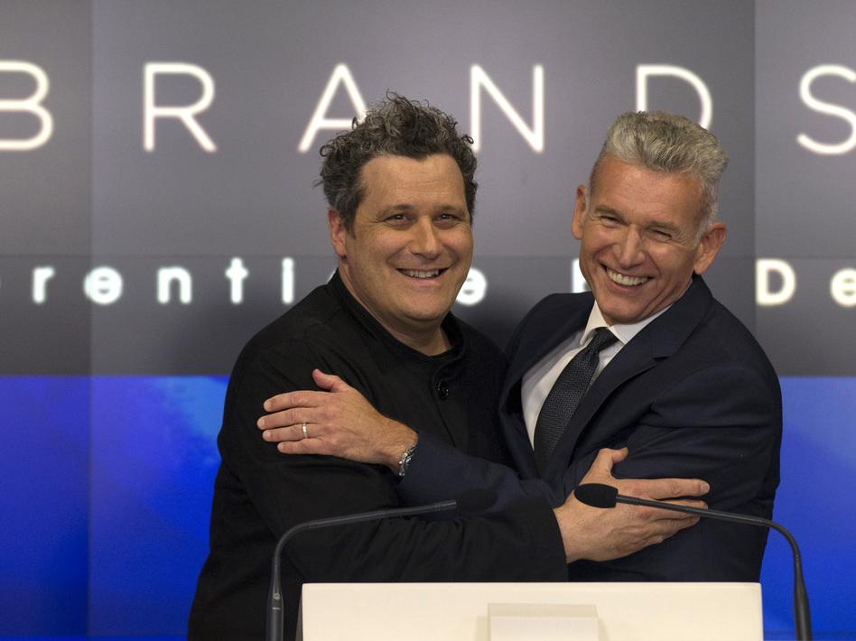 Designer Isaac Mizrahi (left) embraces Robert D'Loren, CEO of Xcel Brands, which once manufactured 70% of its clothes in China. Today that's down to about 20%. The company now manufacturers in a variety of countries, including Indonesia, India and Sri Lanka. (Brendan McDermid/Reuters)