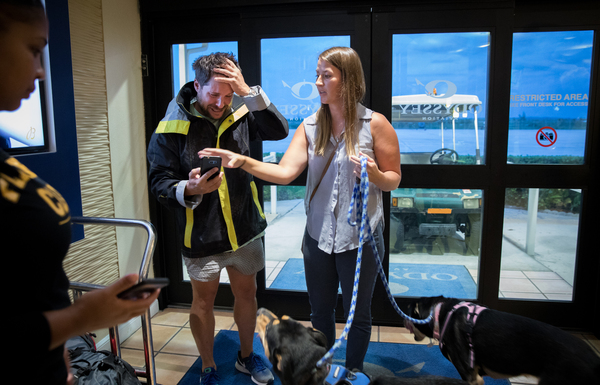 Alex Cepero cries while his friend Cassandra Shipp holds his two dogs upon their arrival from being rescued from Marsh Harbor on the Abaco Islands.