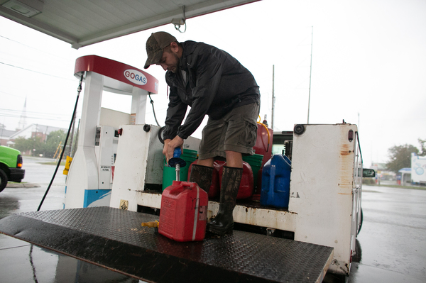 Jessie Avant fills up several gas containers at a gas station in Wilmington, N.C., on Thursday. Hurricane Dorian is churning just off the coast of the Carolinas, flooding areas along the shore of both states with a storm surge that could measure up to 5-8 feet.