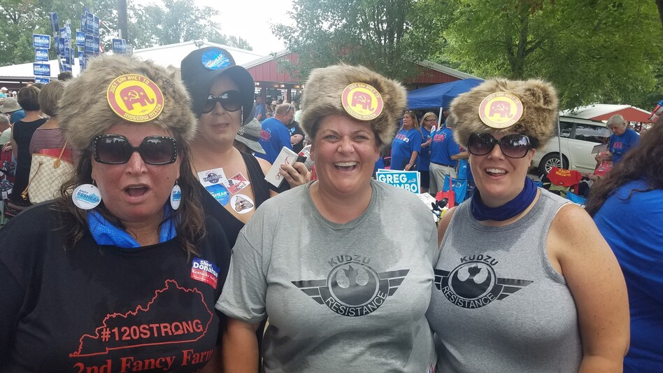 """The August heat at a political event did not deter (from left) Laura Hartke, Christina Trosper and Katie Hancock from wearing their Russian-styled fur hat with buttons saying: """"Say Nyet To Moscow Mitch."""" (Ryland Barton/Kentucky Public Radio)"""