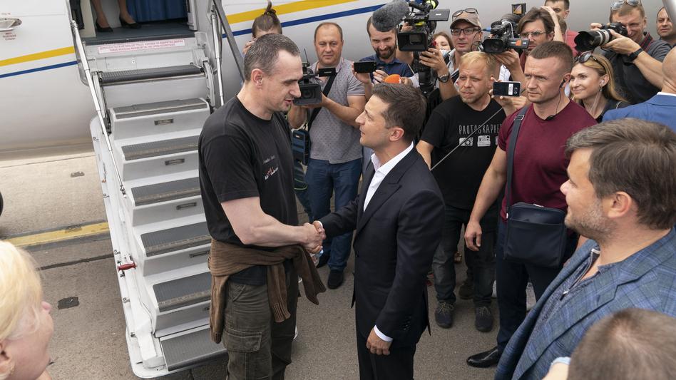 Ukraine's President Volodymyr Zelenskiy (right) greets Ukrainian prisoner filmmaker Oleg Sentsov upon his arrival in Ukraine on Saturday. (Efrem Lukatsky/AP)