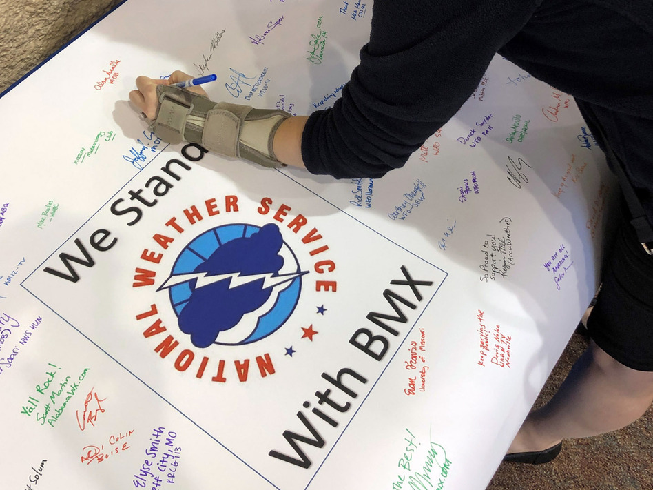 Christina Crowe signs a poster in support of the National Weather Service office in Birmingham, Ala., during a convention of the National Weather Association. (Jay Reeves/AP)