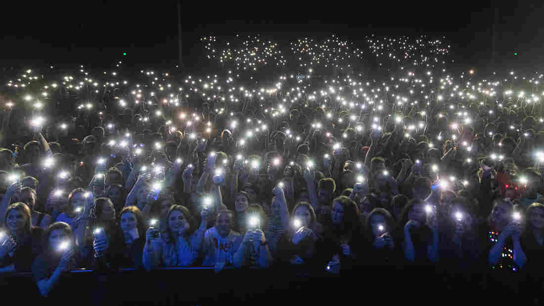 Fans hold up cell phones during a concert.