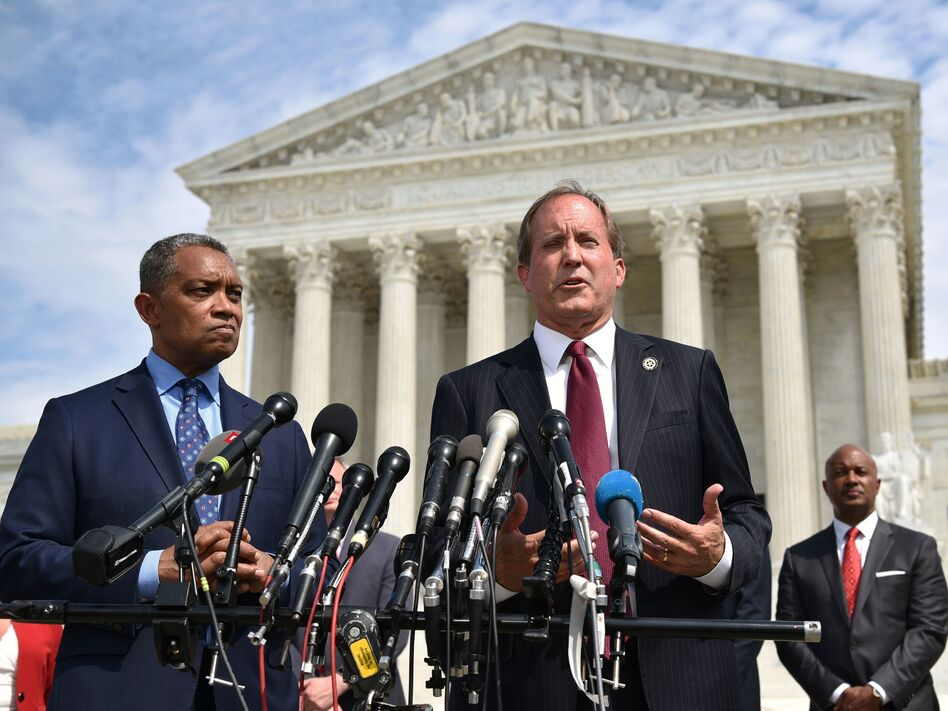 District of Columbia Attorney General Karl Racine (left) and Texas Attorney General Ken Paxton speak Monday about the launch of an antitrust investigation into Google outside the Supreme Court in Washington, D.C. (Mandel Ngan/AFP/Getty Images)