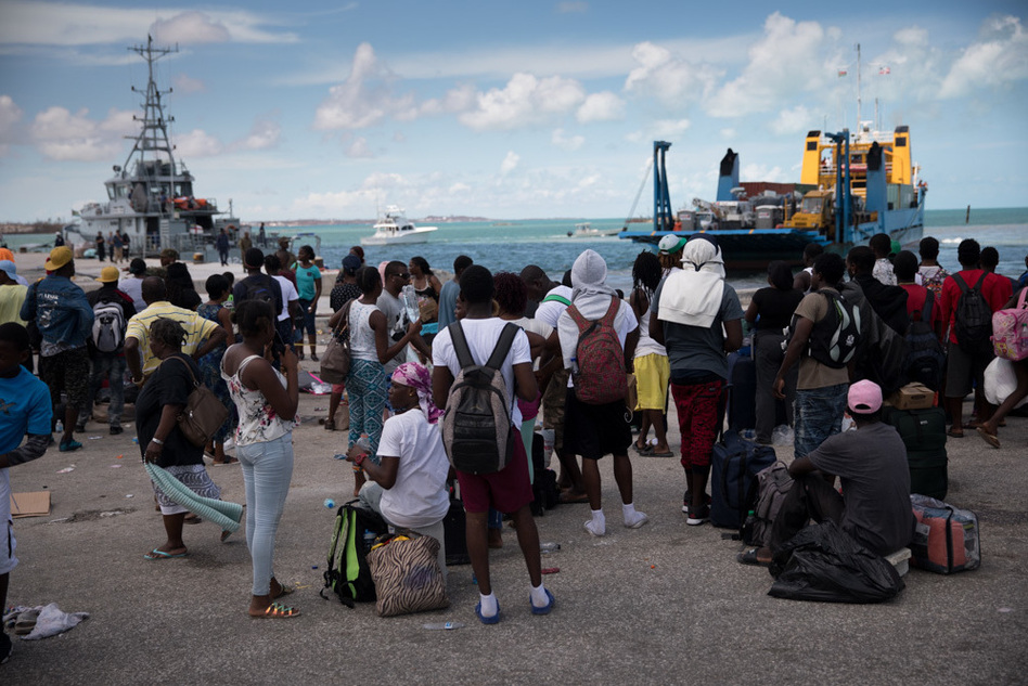 Several hundred Haitians and Bahamians wait at the port of Marsh Harbour in hopes of boarding a boat to Nassau on Friday. (Cheryl Diaz Meyer for NPR)
