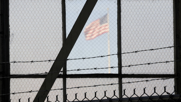 An NPR investigation finds that the military court and prison at Guantánamo Bay, Cuba, have cost taxpayers billions of dollars, with billions more expected. (Above) An American flag is seen through the war crimes courtroom at the U.S. naval base at Guantánamo Bay on Oct. 17, 2012.
