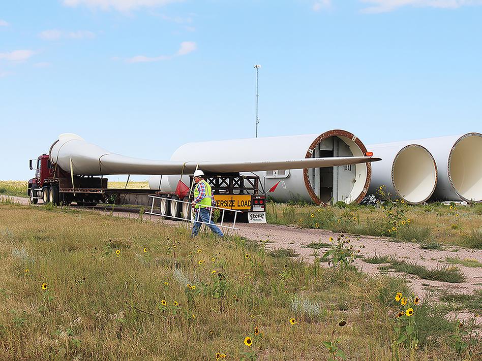 Rob Van Vleet secures a wind turbine blade onto an oversize truck at the Kimball Wind Farm in southwest Nebraska. (Christina Stella/Harvest Public Media)