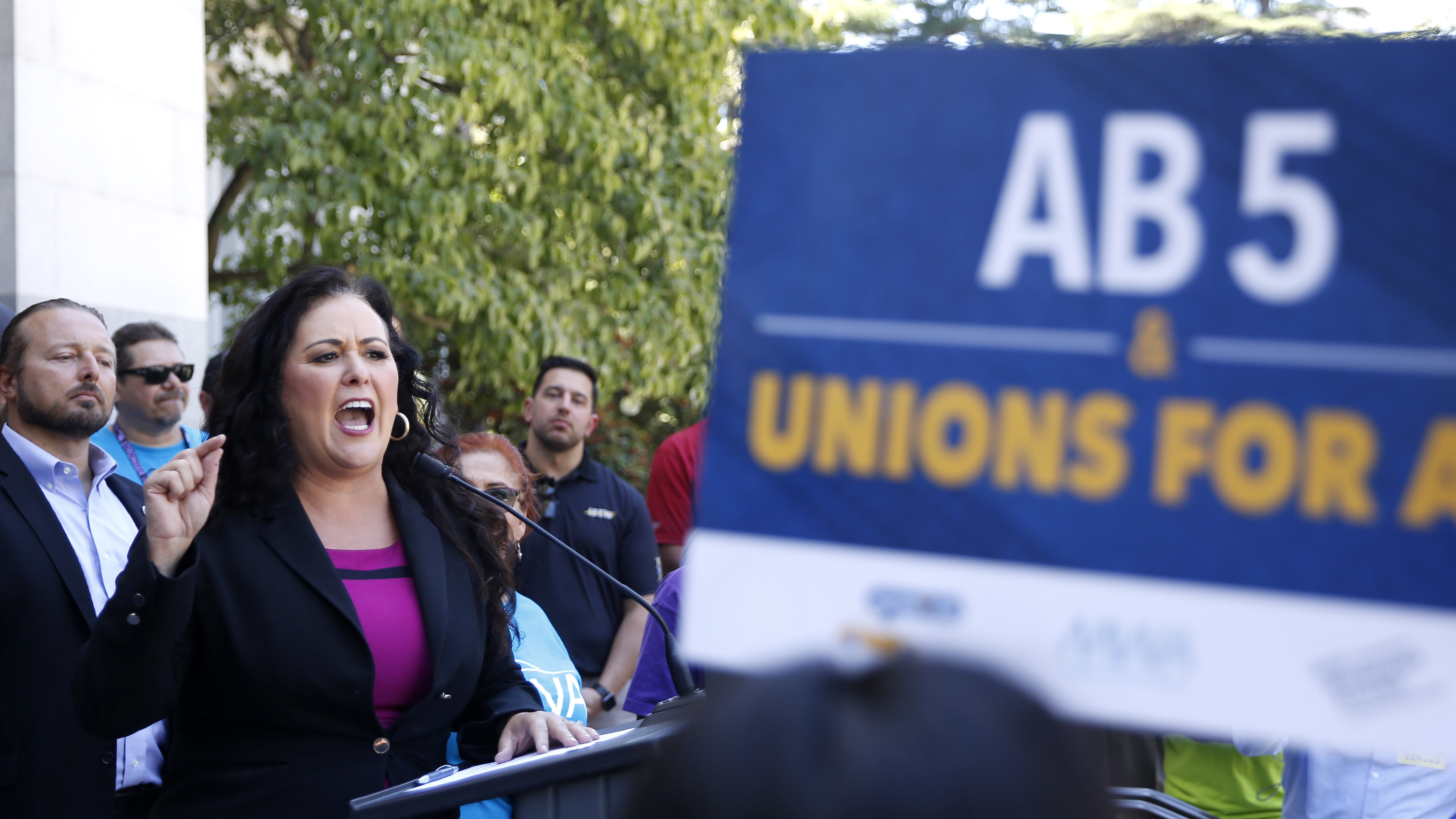 Democratic Assemblywoman Lorena Gonzalez speaks at a July rally for independent contractors in Sacramento, Calif. The measure that passed Tuesday in the state Senate requires companies such as Lyft and Uber to turn many contract workers into employees.