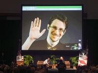 Edward Snowden appears on a live video feed broadcast from Moscow at an event sponsored by the ACLU Hawaii in Honolulu on Feb. 14, 2015.