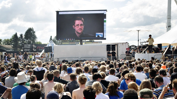 """Former NSA contractor Edward Snowden, on a video link in Moscow, speaks to the crowd on a giant screen at festival in Roskilde, Denmark, in 2016. """"You are being watched all the time and you have no privacy,"""" Snowden said."""