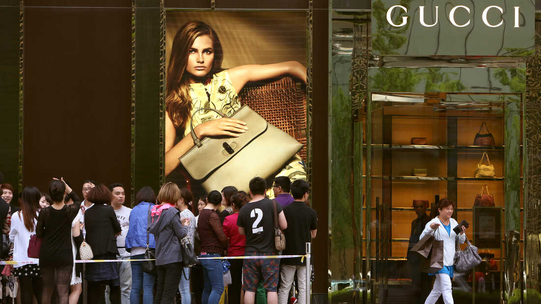 SHANGHAI, CHINA - Customers wait outside Gucci Store in Golden Eagle Shopping Center in Shanghai, China.