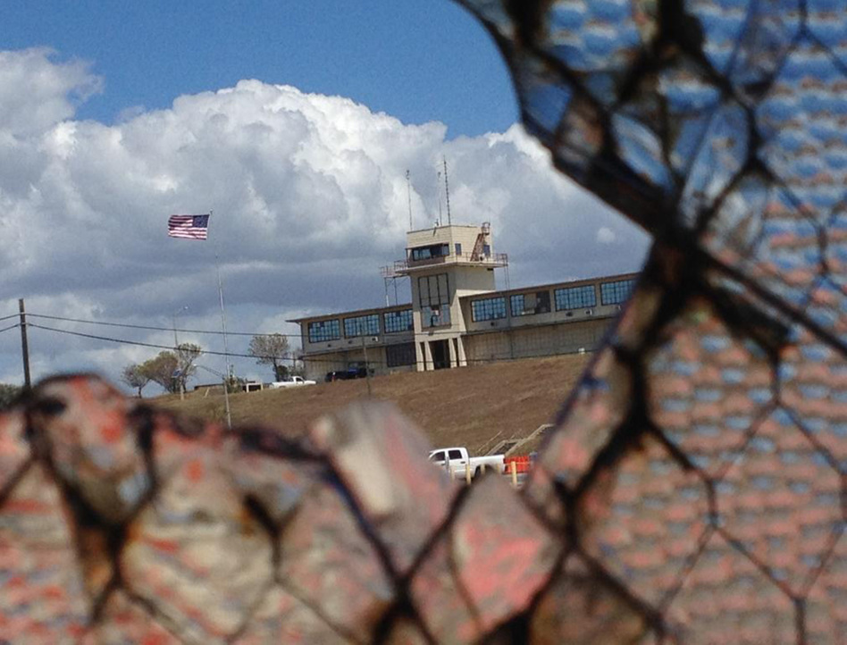 An NPR investigation finds that the military court and prison at Guantánamo Bay, Cuba, have cost taxpayers billions of dollars, with billions more expected. The war court headquarters at Camp Justice, as seen through a broken window at an obsolete air hangar at the U.S. Navy base at Guantánamo Bay, Cuba, on February 28, 2015. (Emily Michot//Miami Herald/Tribune News Service via Getty Images)