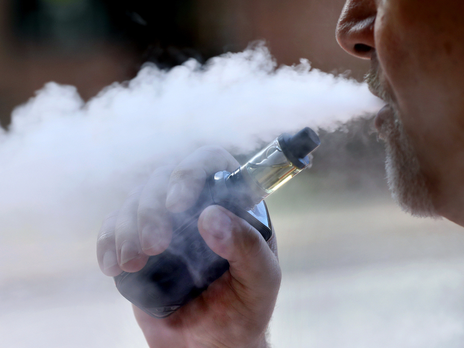 A man exhales while smoking an e-cigarette. New York Gov. Andrew Cuomo said the state will issue an emergency regulation banning certain flavored products amid a health scare linked to vaping. (Robert F. Bukaty/AP)