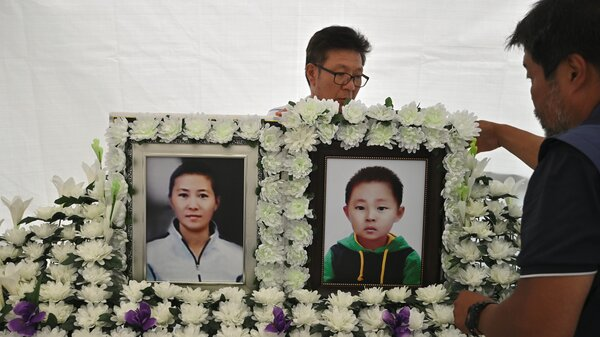 A man sets up portraits of North Korean defector Han Seong-ok and her 6-year-old son, who are believed to have died from starvation, at a makeshift shrine in downtown Seoul on Aug. 28.