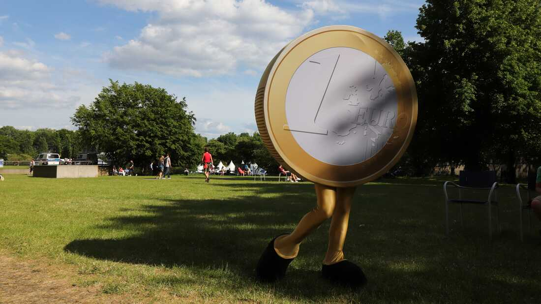This picture taken on May 26, 2019, shows a person dressed as an euro coin in the garden of the German federal bank in Frankfurt am Main, western Germany.