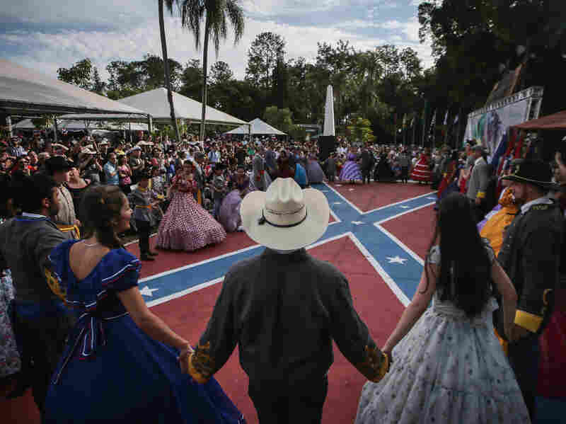 People in traditional Confederate costumes hold hands between dances at the annual Festa Confederada (or Confederate Party) on April 24, 2016 in Santa Barbara d'Oeste, Brazil. The festival is put on by Brazilian descendants of families who fled from the southern United States to Brazil during Reconstruction.