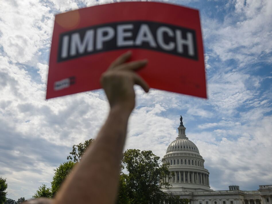 A protester holds up a sign in favor of impeachment outside the U.S. Capitol building on Thursday. (Andrew Caballero-Reynolds/AFP/Getty Images)