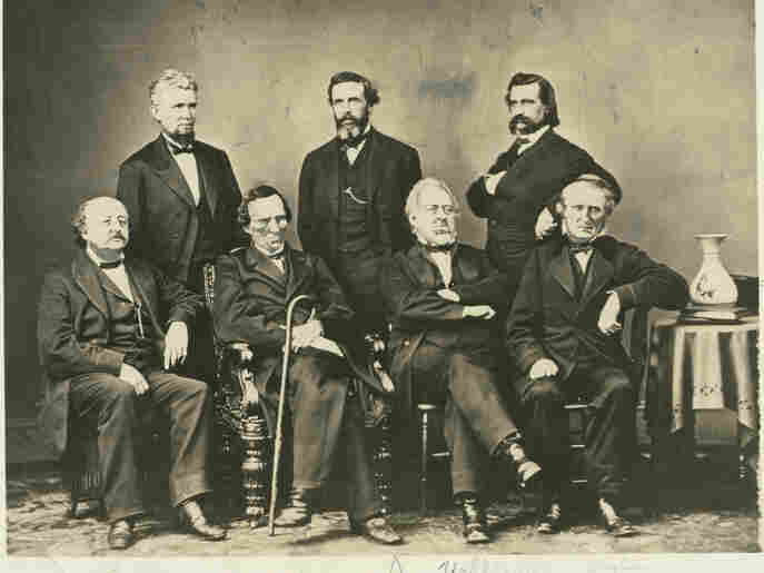 The Johnson Impeachment Committee produced the charges that eventually became the eleven articles of impeachment against President Johnson. Most of the articles centered on the president's alleged violation of the Tenure of Office Act. Left to right, seated: Benjamin F. Butler, Thaddeus Stevens, Thomas Williams, John A. Bingham. Standing: James F. Wilson, George S. Boutwell, John A. Lo