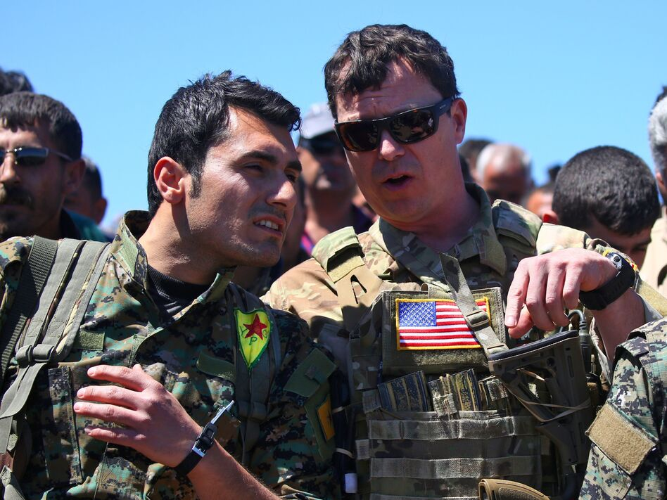 President Trump's plan for the Turkish-Syrian border contradicts recommendations from top officials in the Pentagon and the State Department. In this 2017 photo, a U.S. officer from the coalition against ISIS speaks with a fighter from the Kurdish People's Protection Units at the site of Turkish airstrikes near the northeastern Syrian Kurdish town of Derik. (Delil Souleiman/AFP/Getty Images)