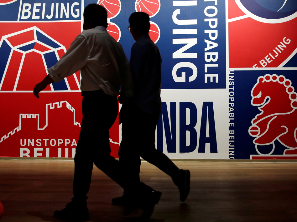 Men walk past a poster at an NBA exhibition in Beijing on Oct. 8. (Jason Lee/Reuters)