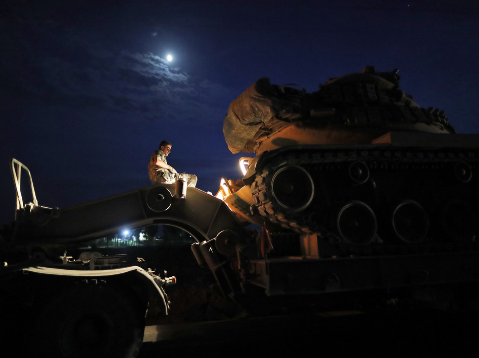 A Turkish army officer prepares to unload a tank from a truck to its new position on the Turkish side of the border between Turkey and Syria, in Sanliurfa province, southeastern Turkey, on Tuesday. (Lefteris Pitarakis/AP)