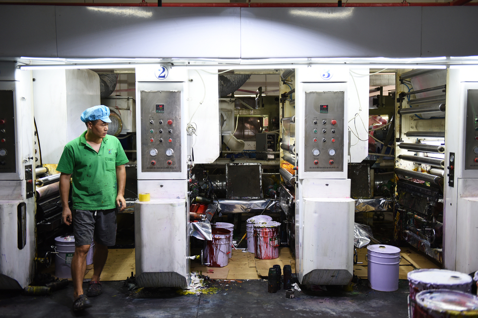 Workers in green polo shirts and blue caps monitor machines making plastic products at the Dongguan Fangjie Printing and Packaging Company. (Jolie Myers/NPR)