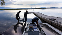 Mohammed Bawazeer (left) and Ian Riley carry a battery that will power the aeration system on Upper Klamath Lake for 32 hours, even if the sun isn't shining.