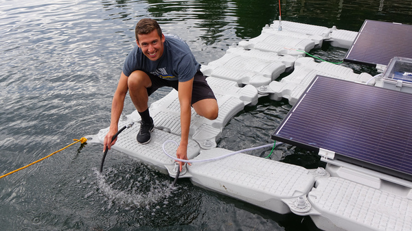 Oregon Institute of Technology student Juan Billarreal holds the aeration hose that will add dissolved oxygen to Upper Klamath Lake.