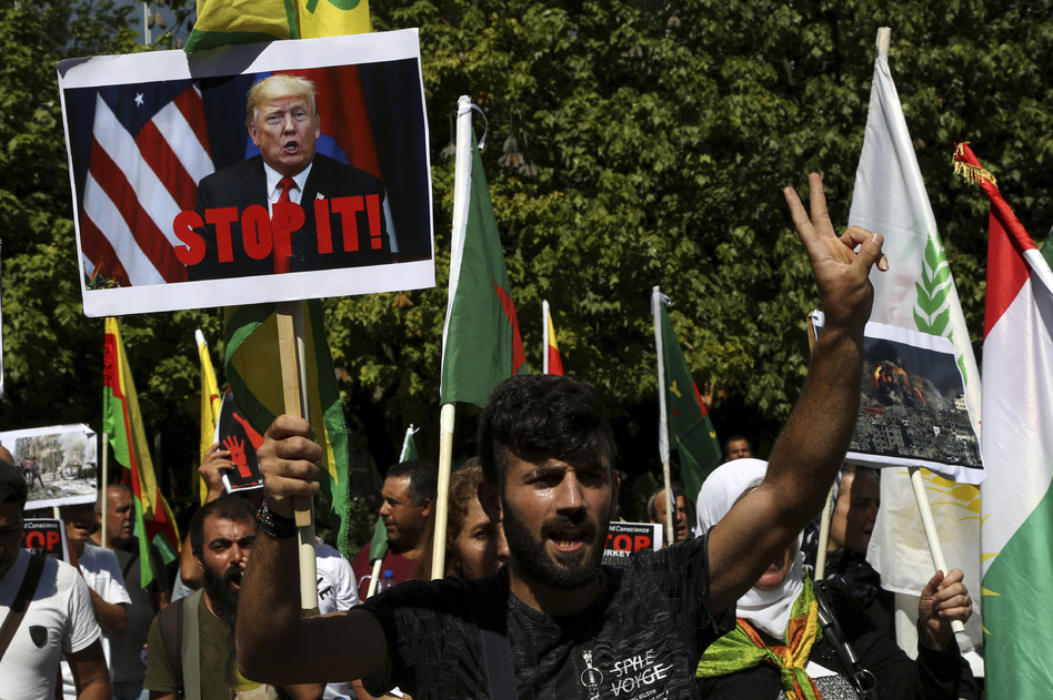 A Kurd living in Cyprus shouts slogans in front of the U.S. Embassy in Nicosia, Cyprus, on Thursday to protest Turkey's offensive into Syria. The protesters chanted slogans condemning Turkey's military action and urging the withdrawal of Turkish forces. (Petros Karadjias/AP)
