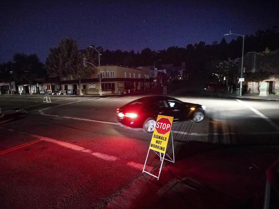 A car drives through a darkened Montclair Village during the power shutdown in Oakland, Calif., triggered by dry, windy weather. (Noah Berger/AP)