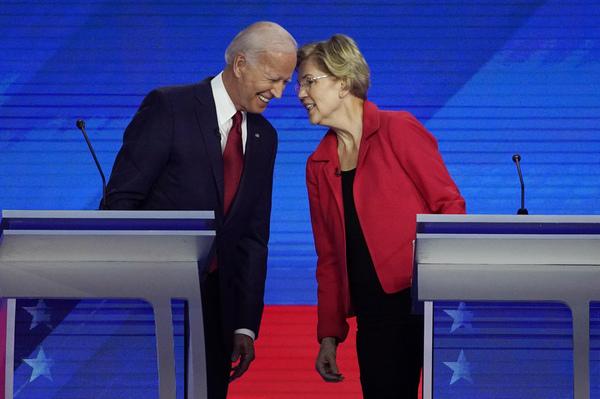 Democratic presidential candidates Joe Biden and Sen. Elizabeth Warren, D-Mass., talk and touch heads before the September Democratic presidential primary debate.