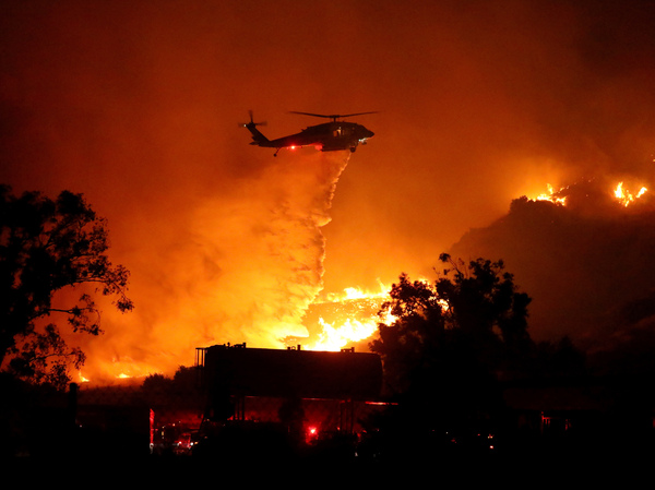Water is dropped on a large brush fire in the early morning hours Friday in Sylmar, Calif. At least 25 structures have been destroyed.
