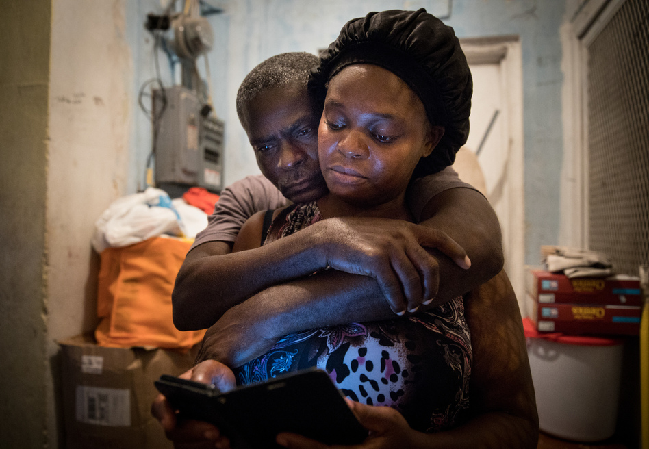 A month after Hurricane Dorian devastated the Bahamas, Sherrine Petit Homme LaFrance gets a hug from husband Ferrier Petit Homme. The storm destroyed their home on Grand Abaco Island. They are now living with China Laguerre in Nassau. (Cheryl Diaz Meyer for NPR)