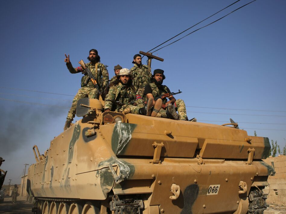 Turkey-backed Syrian fighters sit atop an armored personnel carrier in the southwestern neighborhoods of the border Syrian town of Tal Abyad on Sunday. The U.S. plans to evacuate its troops from northern Syria amid the Turkish offensive. (Bakr Alkasem/AFP via Getty Images)