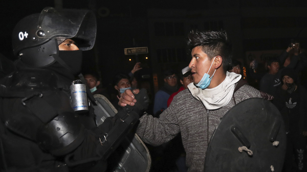 A protester shakes hands with a security officer in Quito, Ecuador, on Sunday as they celebrate the government