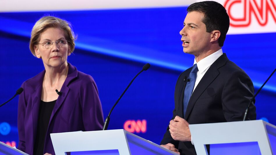 Massachusetts Sen. Elizabeth Warren looks on as South Bend, Ind., Mayor Pete Buttigieg speaks during Tuesday's Democratic presidential debate. Warren's policy positions were described as unrealistic and expensive by her rivals in the Democratic debate. (Saul Loeb/AFP via Getty Images)