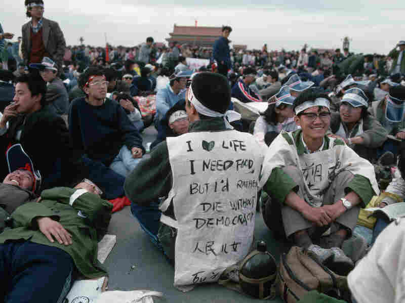 """A young student protester in Tiananmen Square wears a sign which reads: """"I love life, I need food, but I'd rather die without democracy."""" On June 3, 1989, Chinese paramount leader Deng Xiaoping ordered a crackdown and unknown numbers of demonstrators and bystanders were killed."""