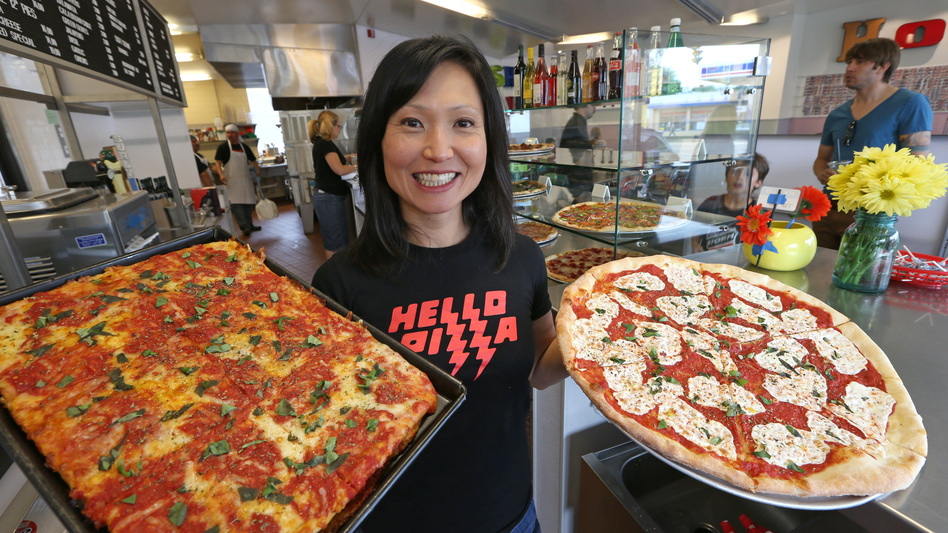 """Ann Kim, owner of Hello Pizza in Edina, Minn., holds a Sicilian pan pie and a Hello Rita pizza. """"Women can make progress in pizza that is harder in the macho restaurant world,"""" Kim says. (Bruce Bisping/Star Tribune via Getty Images)"""