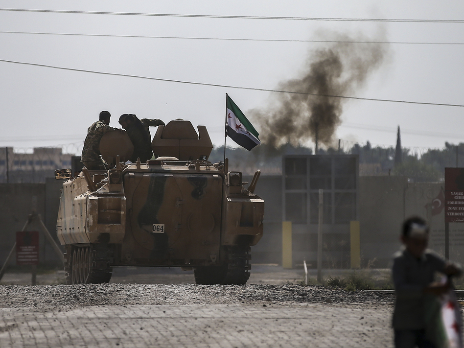 Fighting continued early Friday in a northeast Syrian border town at the center of the fight between Turkey and Kurdish forces, despite a U.S.-brokered cease-fire that went into effect overnight. (Emrah Gurel/AP)