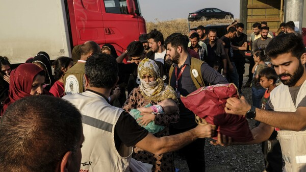 Syrians fleeing the Turkish incursion in northeastern Syria receive bedding materials as they arrive at a camp on Thursday in Dohuk, Iraq.
