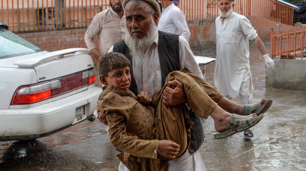 A volunteer carries an injured youth to a hospital after an explosion that killed at least 62 people in the Haska Mina district of Nangarhar province Friday.