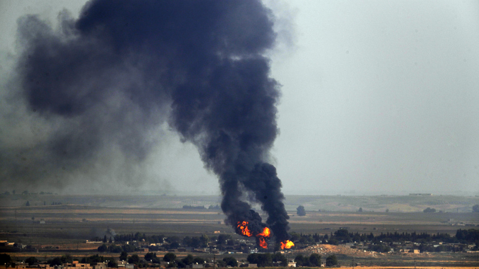 In this photo taken Thursday, flames and smoke billow from a fire on a target in Ras al-Ayn, Syria. This is the result of shelling by Turkish forces, the same day Turkey and the U.S. were negotiating a cease-fire agreement. (Cavit Ozgul/AP)